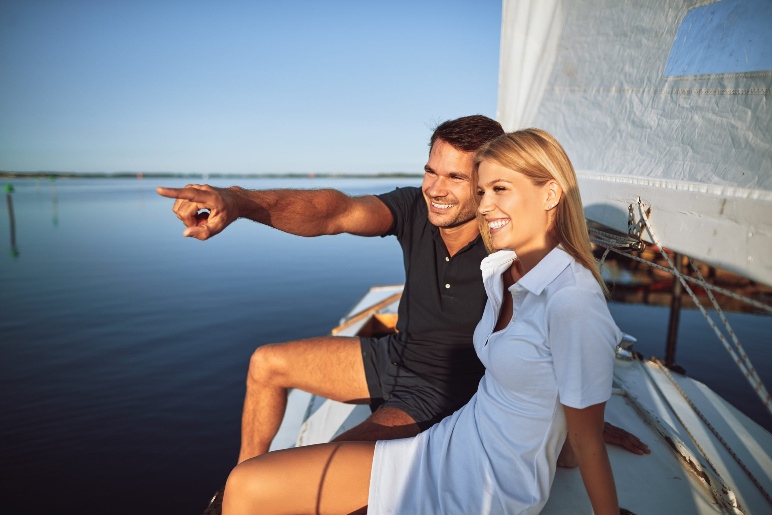 Young man pointing to something on the ocean horizon to his wife while sitting on the deck of their boat enjoying the day sailing